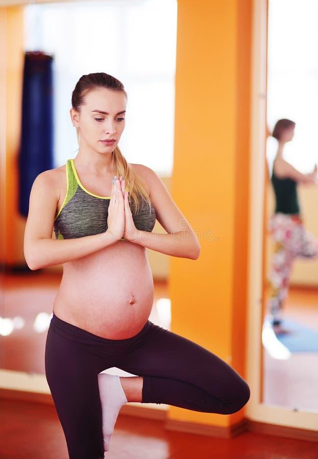 La mujer embarazada realiza ejercicios aeróbicos o asanas con un grupo de yoga en un cuarto de la aptitud fotos de archivo