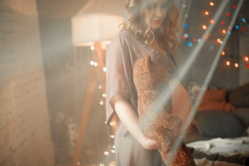 La mujer embarazada se coloca con el oso de peluche en peignoir abierto Visión thr imagenes de archivo