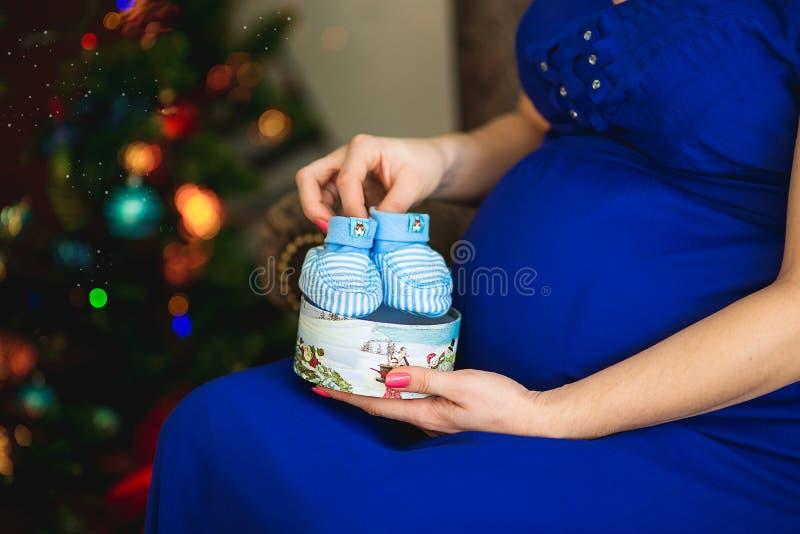 La mujer embarazada sostiene los botines de los niños disponibles imagen de archivo libre de regalías