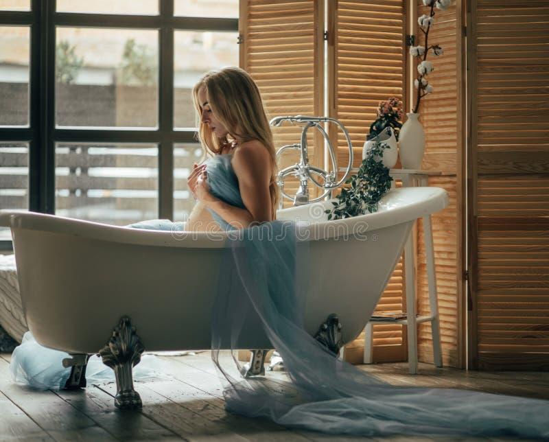 La mujer embarazada toma un baño imagenes de archivo