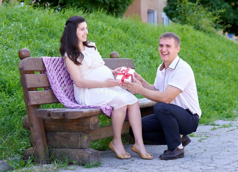 La mujer embarazada toma un regalo de su marido, familia feliz, pares en parque de la ciudad, estación de verano, hierba verde y  fotografía de archivo