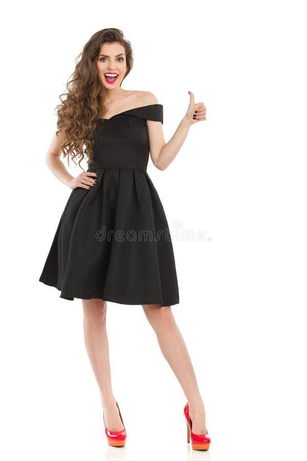 La mujer emocionada elegante en vestido negro da el pulgar para arriba fotos de archivo
