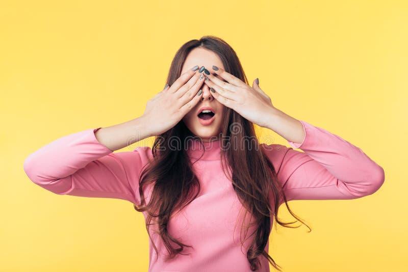 La mujer emocionada Surprised se cerró los ojos con las manos que esperaban sorpresa aislados en fondo amarillo fotografía de archivo libre de regalías