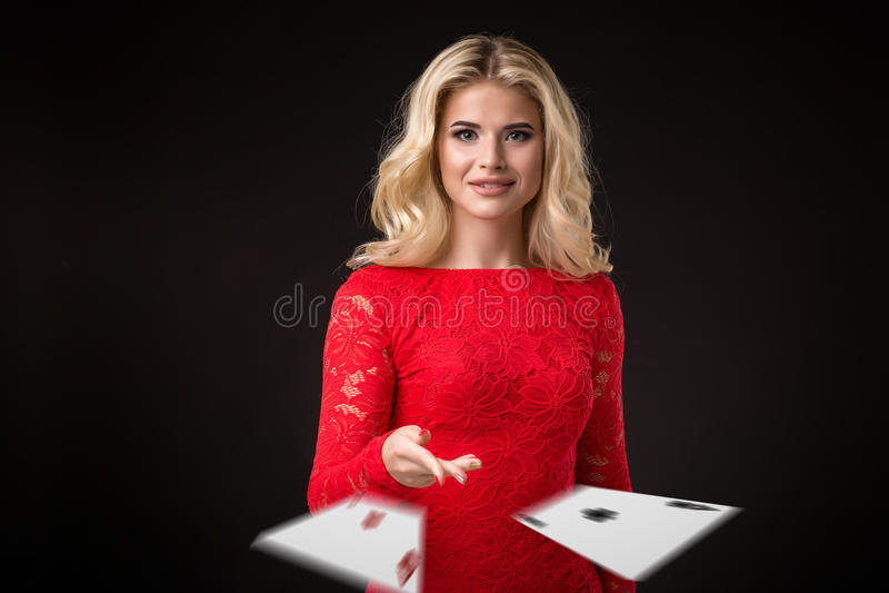 La mujer emocional hermosa joven lanza tarjetas en un fondo negro en el estudio póker imagenes de archivo