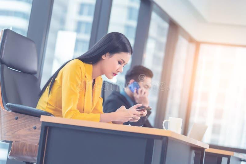 La mujer en amarillo está utilizando el dispositivo móvil para mandar un SMS y para utilizar a Internet fotografía de archivo libre de regalías