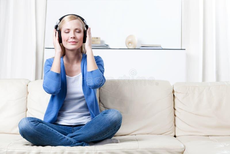 La mujer en auriculares escucha la música fotos de archivo libres de regalías