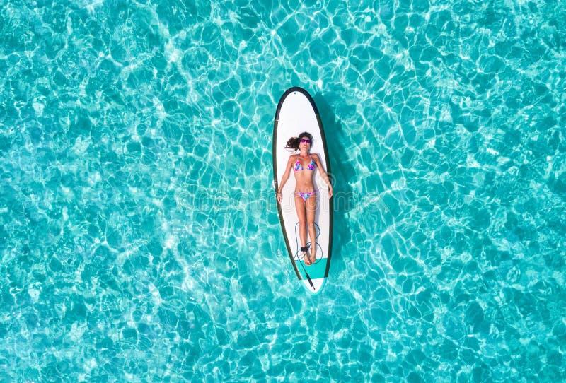 La mujer en bikini está tomando el sol en una tabla hawaiana, fotografía de archivo libre de regalías