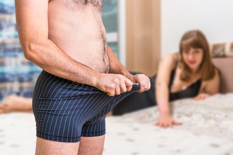 La mujer en cama y hombre en ropa interior está mirando dentro foto de archivo libre de regalías