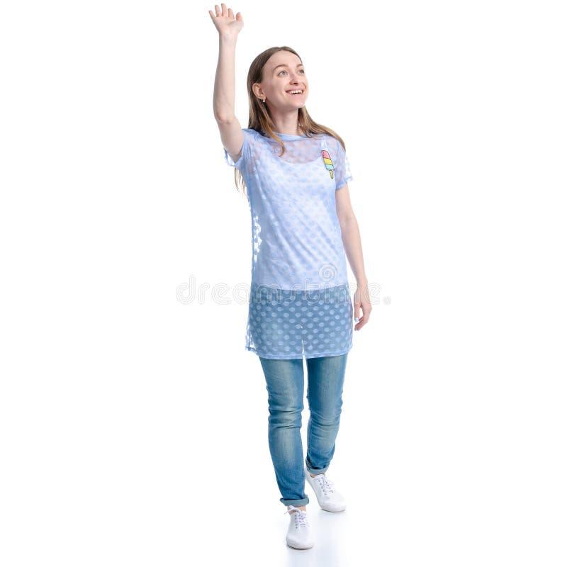 La mujer en caminar de los tejanos va a sonreír mirando la mano que agita fotos de archivo
