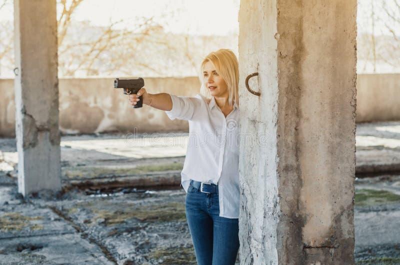 La mujer en la camisa blanca en un edificio abandonado tira una pistola foto de archivo libre de regalías