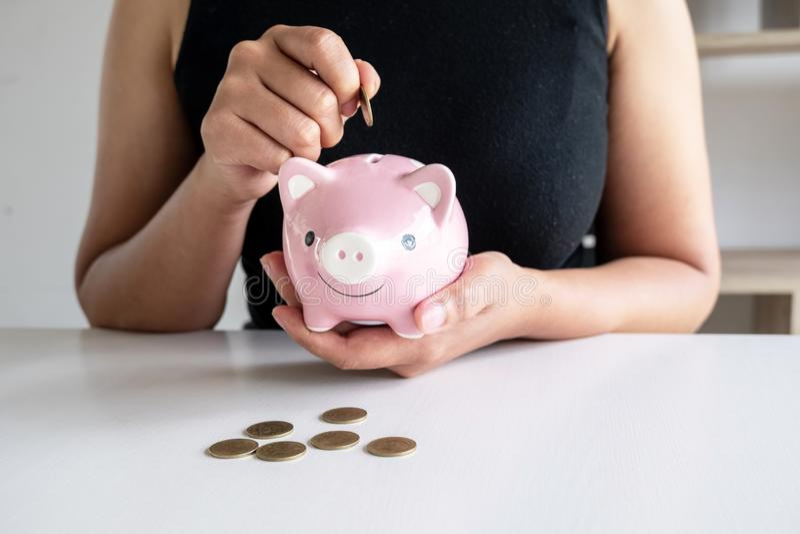 La mujer en camisa negra enseña a equipos a poner la moneda en la hucha rosada foto de archivo libre de regalías