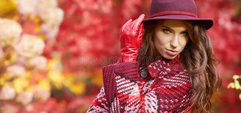 La mujer en capa con el sombrero y la bufanda en otoño parquean fotografía de archivo libre de regalías