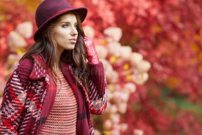 La mujer en capa con el sombrero y la bufanda en otoño parquean foto de archivo