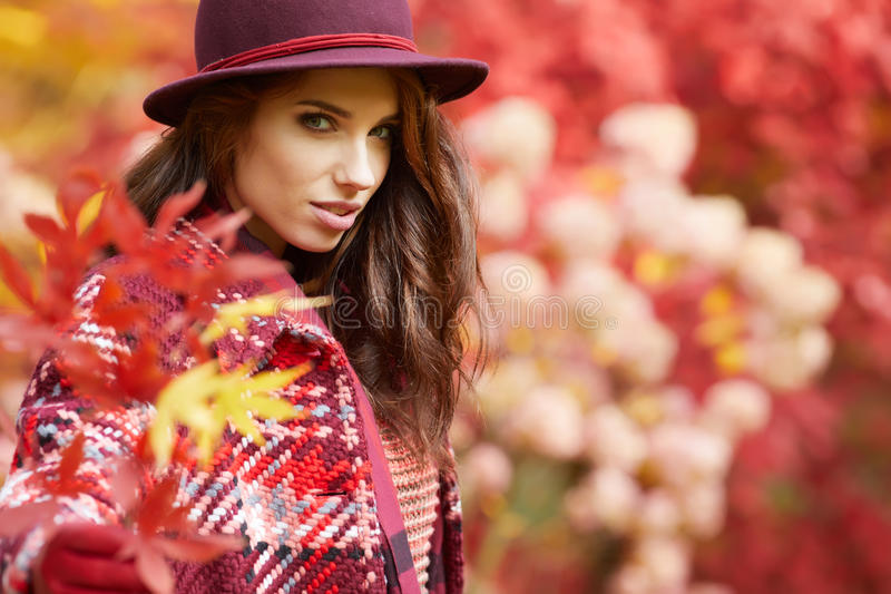 La mujer en capa con el sombrero y la bufanda en otoño parquean fotos de archivo