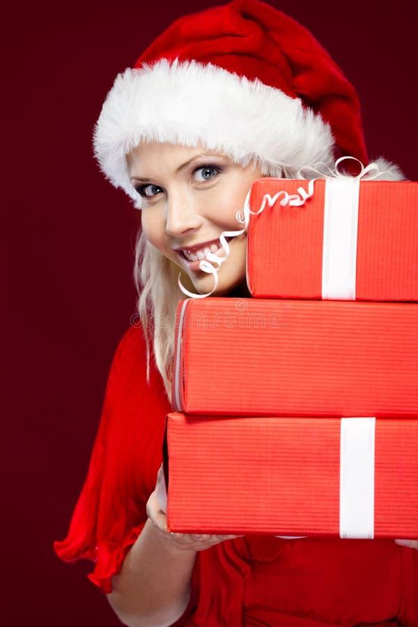 La mujer en casquillo de la Navidad lleva a cabo un conjunto de presentes fotografía de archivo libre de regalías