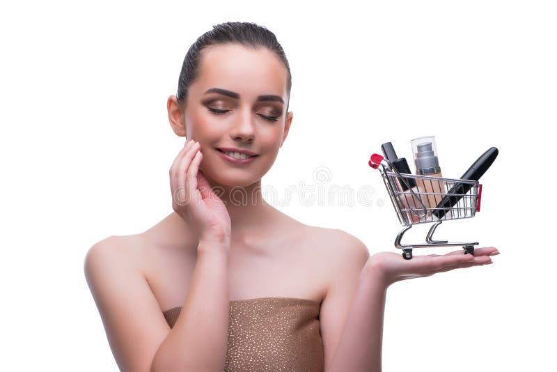 La mujer en concepto de la belleza con compone sostener el carro de la compra fotografía de archivo