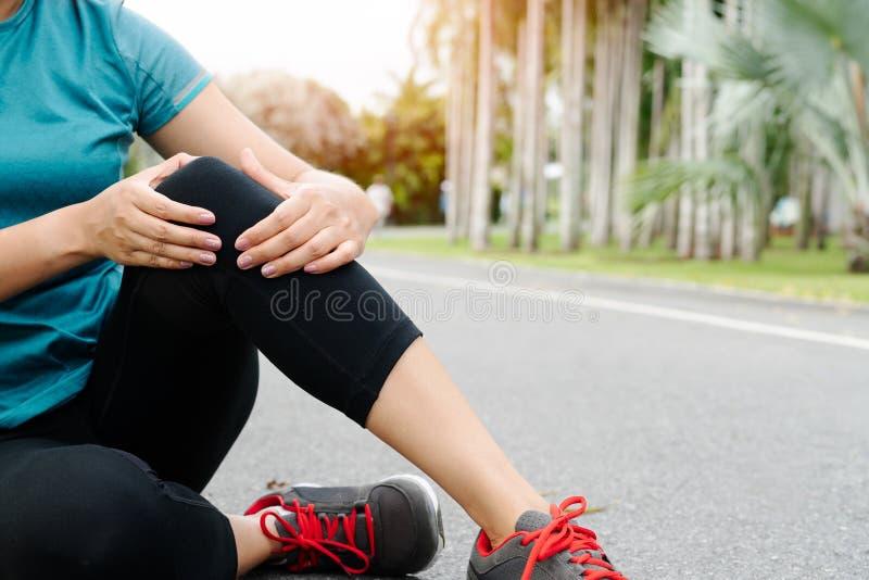 La mujer en ejercicio siente dolor de rodilla. Concepto de actividades de ejercicio al aire libre foto de archivo