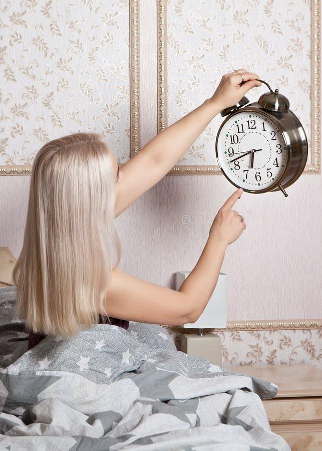 La mujer en el dormitorio con un gran despertador en la mano muestra el momento de despertar fotografía de archivo libre de regalías