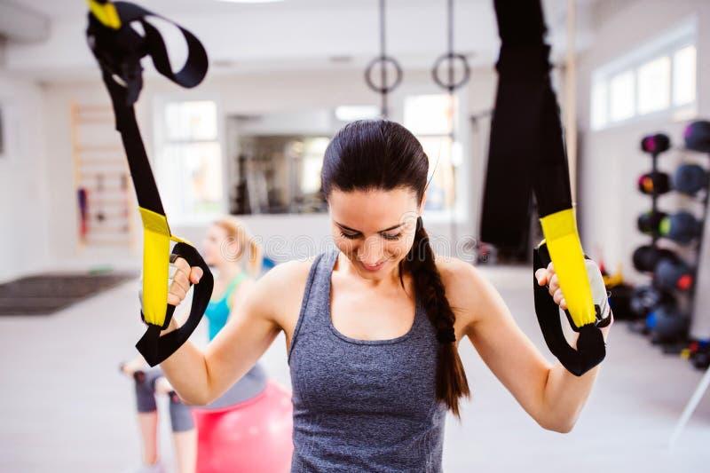 La mujer en el entrenamiento del gimnasio arma con las tiras de la aptitud del trx fotografía de archivo libre de regalías