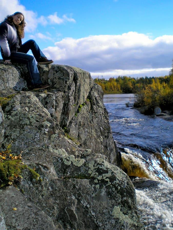 La mujer en el gris oscila cerca de la cascada imagenes de archivo