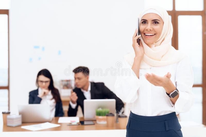 La mujer en el hijab se coloca en el centro de atención telefónica imagen de archivo