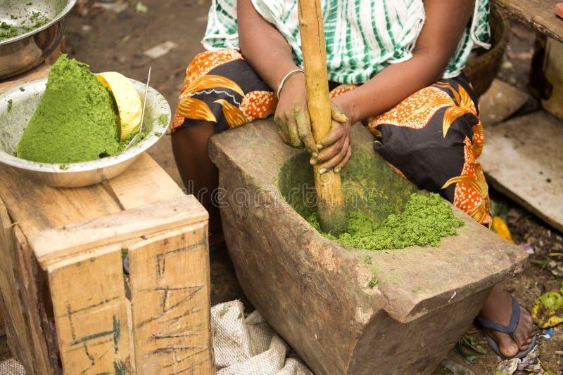 La mujer en el mercado para machacarlos en las herramientas primitivas de las especias, Nosi sea, Madagascar imágenes de archivo libres de regalías