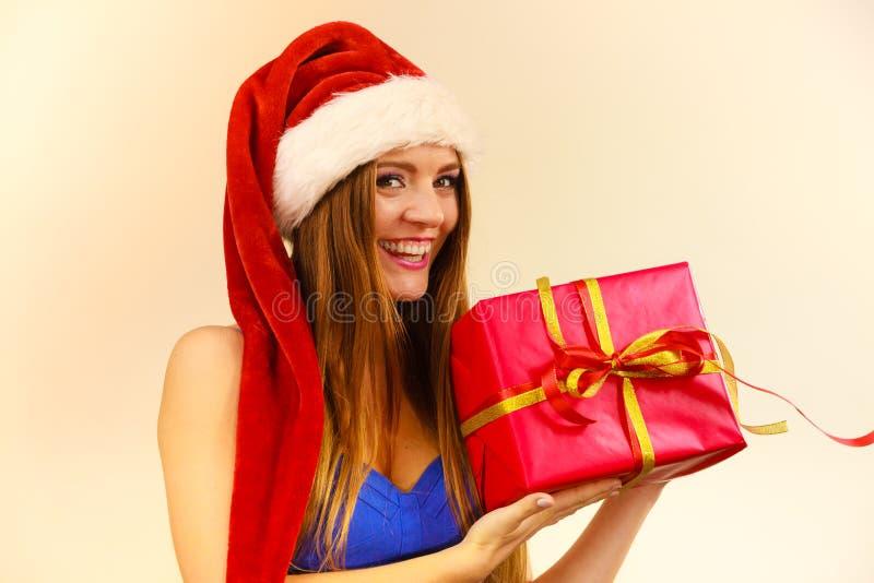 La mujer en el sombrero de Papá Noel sostiene la caja de regalo Tiempo de la Navidad imagen de archivo libre de regalías