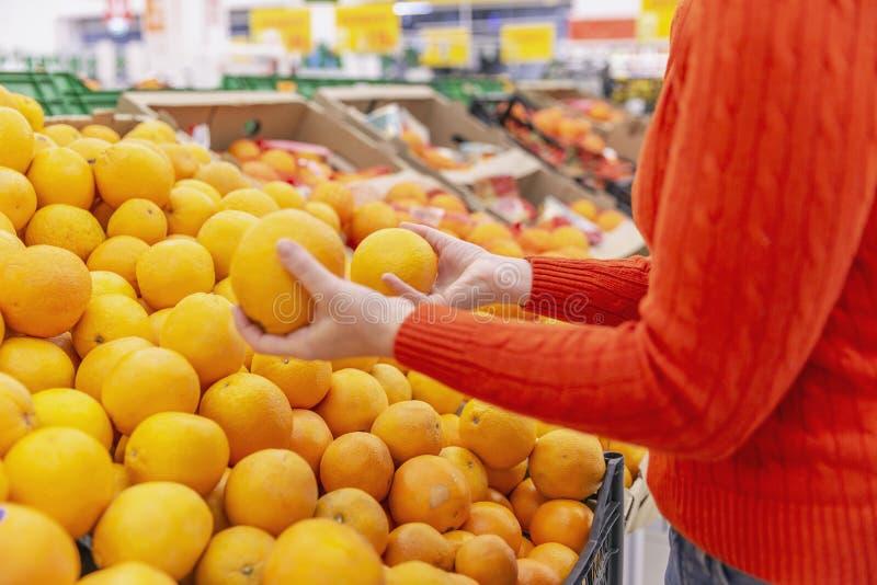La mujer en el supermercado elige las mandarinas imagen de archivo