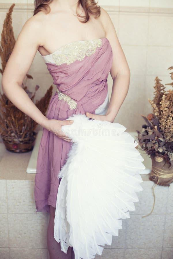 La mujer en el vestido blanco con la correa de la lila y el ángel se van volando a disposición fotografía de archivo