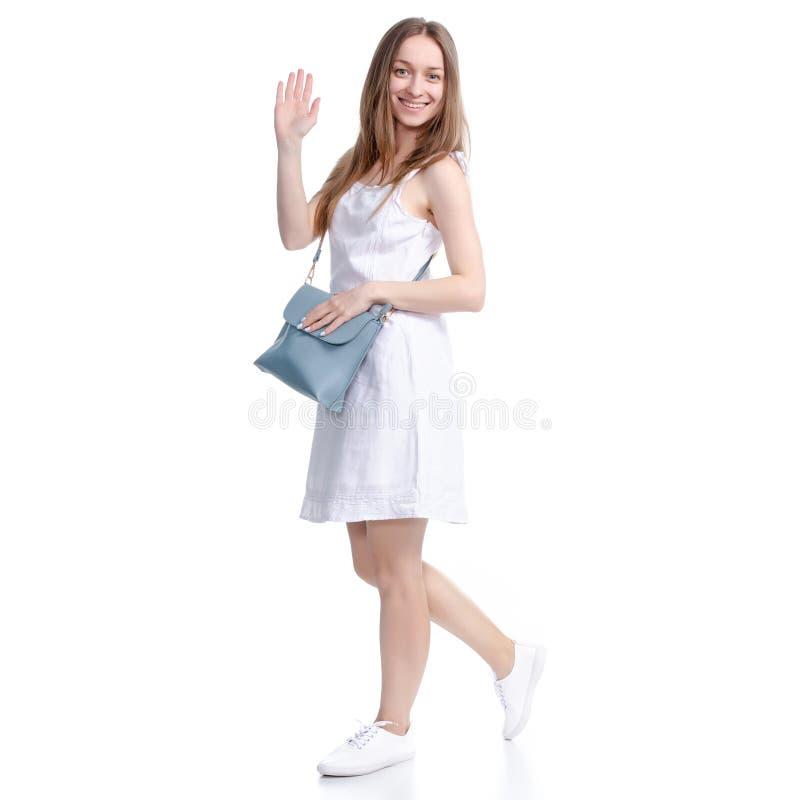 La mujer en el vestido blanco con la mirada del bolso, caminando, va, agitando la mano fotografía de archivo