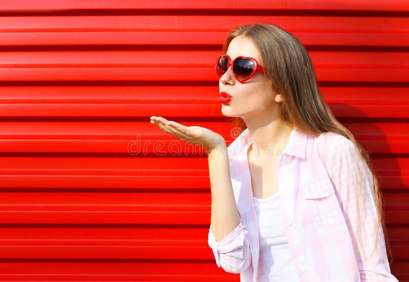 La mujer en gafas de sol rojas envía un beso del aire sobre colorido imagen de archivo libre de regalías