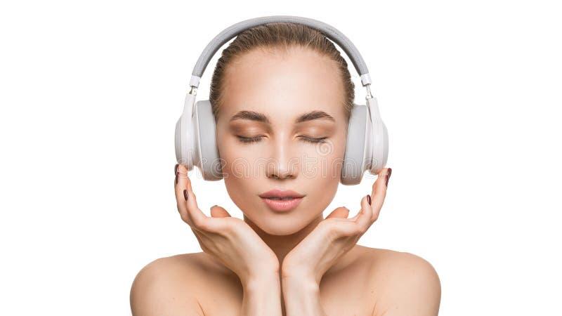 La mujer en los auriculares blancos en el fondo blanco escucha la música con los ojos cerrados foto de archivo libre de regalías