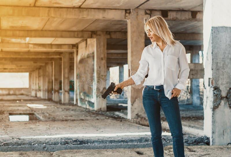 La mujer en los soportes blancos de la camisa en un edificio abandonado, tira un arma fotos de archivo