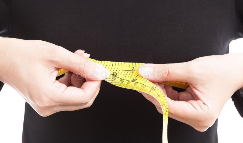 La mujer en negro viste la medición de su pecho con la medición de TA fotos de archivo