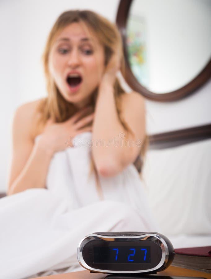 La mujer en pánico mira el reloj por la mañana imagen de archivo libre de regalías