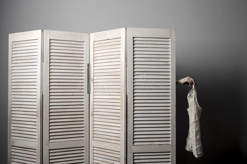 La mujer en parada del vestuario y puesta su brazo sostiene hacia fuera un vestido imagenes de archivo