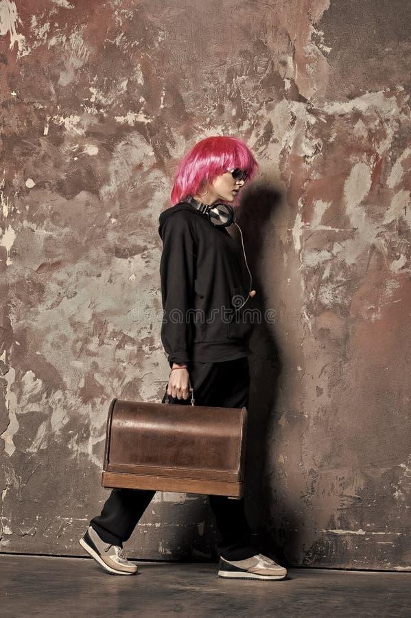 La mujer en la peluca rosada del pelo, auriculares lleva la maleta retra fotos de archivo