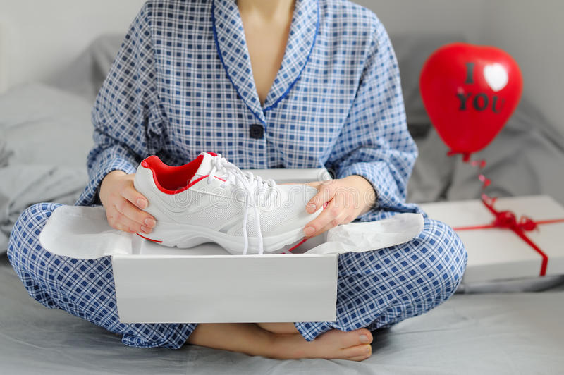 La mujer en pijamas recibió un regalo de los zapatos de los deportes ` S DA de la tarjeta del día de San Valentín imagenes de archivo