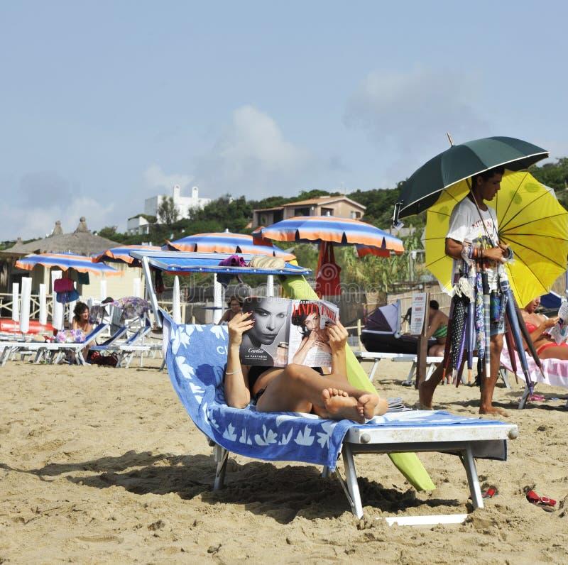 La mujer en la playa se relaja leyendo una revista del chisme En el fondo un vendedor ambulante está caminando fotos de archivo libres de regalías