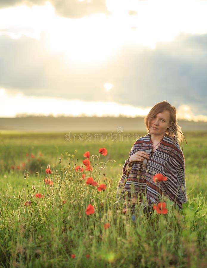 La mujer en poncho se sienta en campo de flor de la puesta del sol imágenes de archivo libres de regalías