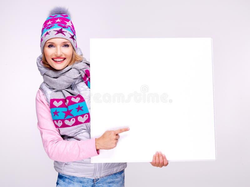 La mujer en prendas de vestir exteriores caliente lleva a cabo la bandera y los puntos en ella imagen de archivo
