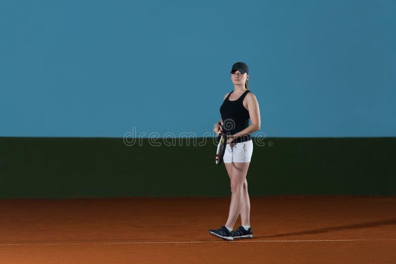 La mujer en ropa de deportes sirve la pelota de tenis fotografía de archivo