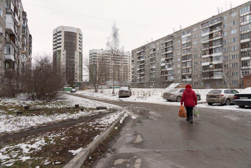 La mujer en ropa roja está caminando a lo largo del camino entre las construcciones de viviendas con los coches parqueados en un  fotos de archivo