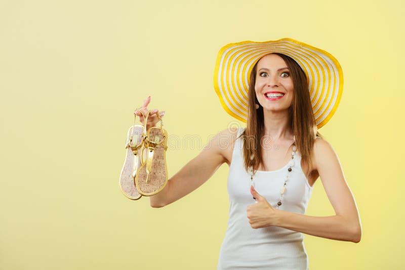 La mujer en sombrero amarillo grande del verano sostiene las sandalias imagen de archivo
