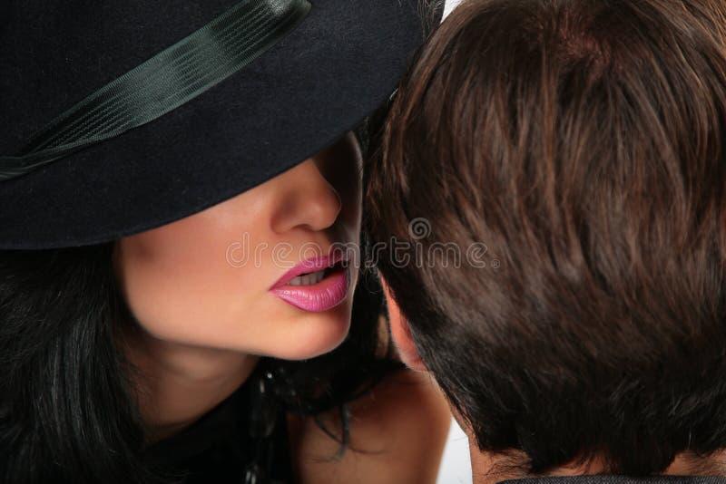 La mujer en sombrero negro dice al hombre fotos de archivo libres de regalías