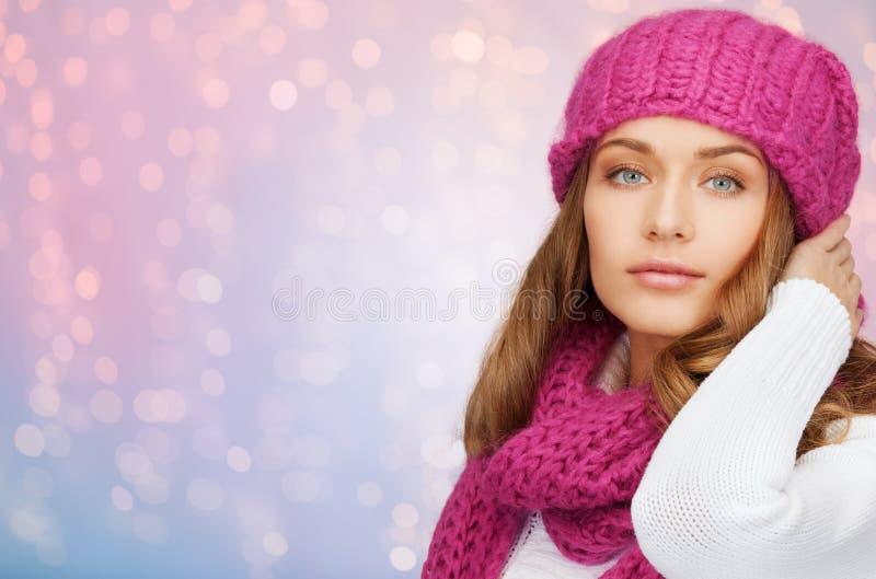 La mujer en sombrero y bufanda sobre rosa enciende el fondo imagenes de archivo