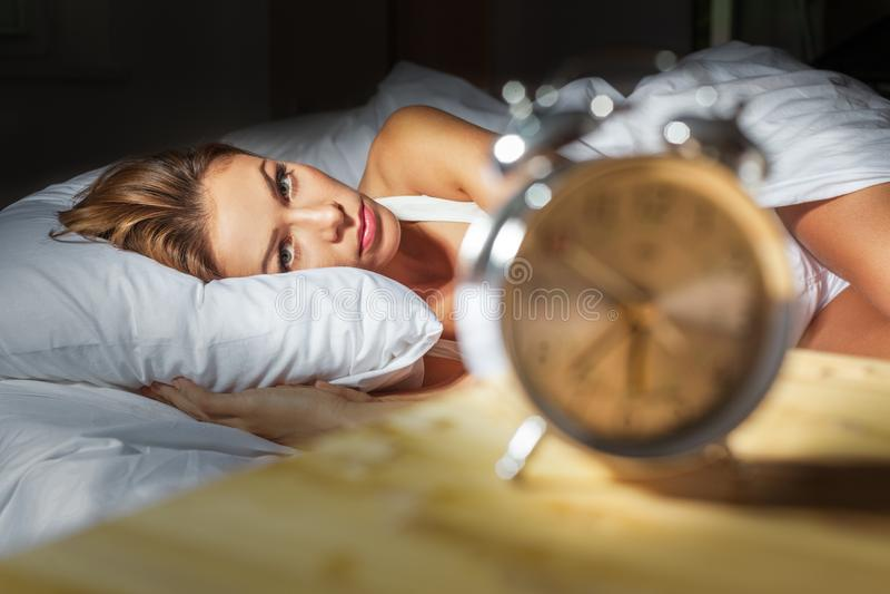 La mujer en su cama con insomnio y pesadillas puede foto de archivo