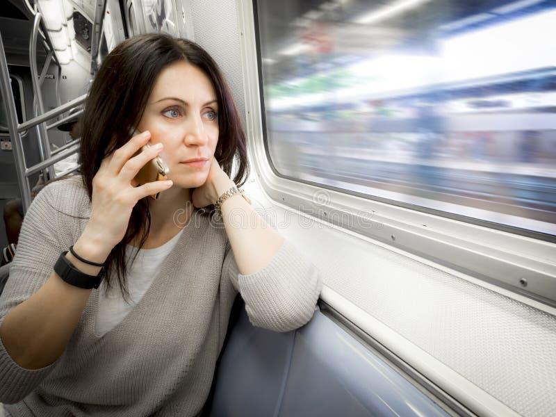 La mujer en su 30s está montando la American National Standard del subterráneo que mira hacia fuera la ventana imagen de archivo libre de regalías