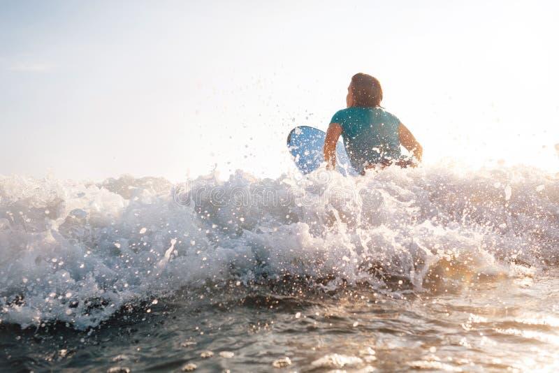 La mujer en la tabla hawaiana nada sobre la onda fotografía de archivo libre de regalías