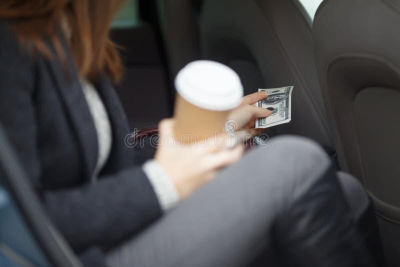 La mujer en taxi produjo el billete de dólar para pagar viaje fotografía de archivo